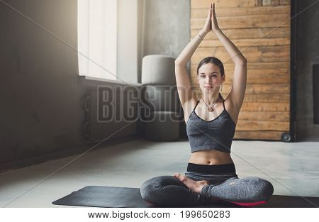 Attractive girl practicing yoga. Young woman in lotus pose doing breathing exercise on mat at sport club interior, copy space