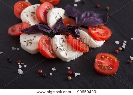 Mozzarella on black stone background. Homemade fresh cheese with tomato and basil, italian cuisine