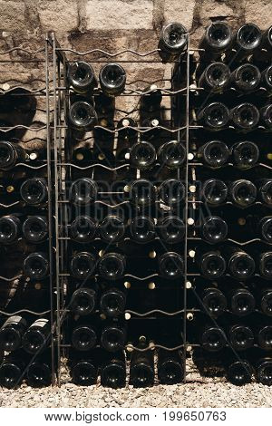 Many bottles of wine in the cellar are stacked in dense rows on the shelves winemaking