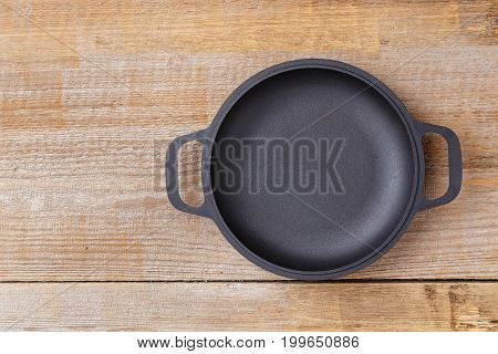 Empty frying pan view from above on an old wooden background space for text