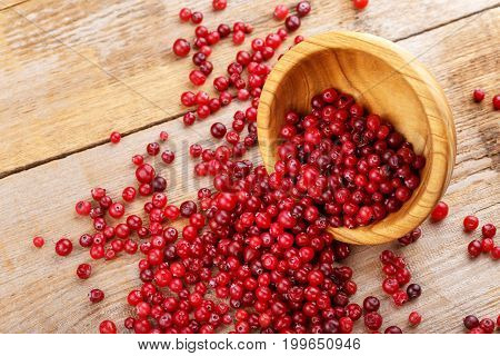 Cranberries in a plate and scattered on a wooden background. Cooking cranberry jam