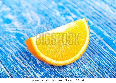 slice of ripe juicy orange on a blue background