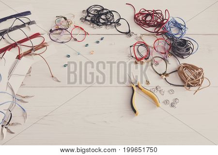 Handmade bracelets making, artisan workplace background. Top view on table with braid, pendants and accessories with pliers, copy space