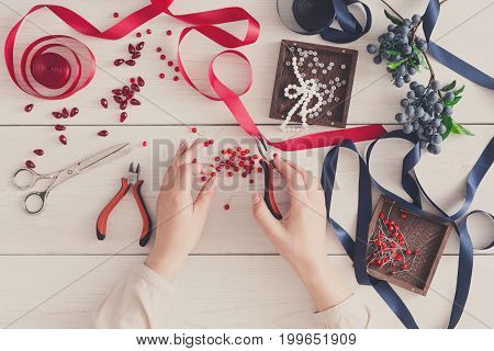 Woman making jewelry, home workshop. Artisan pov, female hands creating accessory with beads and ribbons, top view. Beauty, creativity, handicraft concept