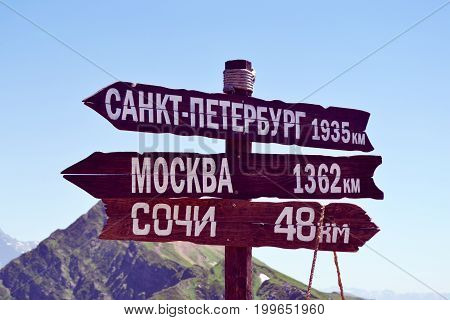 Wooden signpost on top of the Rosa Peak mountain in Rosa Khutor, Alpine Ski Resort, Sochi, Russia. Translation in english: To Saint-Petersburg - 1935 km, to Moscow - 1362 km, to Sochi - 48 km