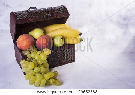 Open chest stuffed with fruit like grapes pears peaches bananas