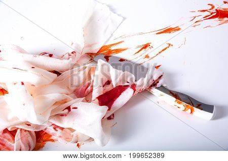 A Knife, blood and bandages on a neutral background.