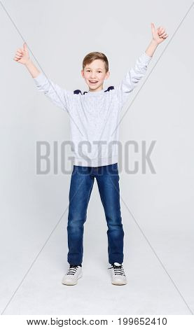 Full length portrait of cheerful boy showing thumbs up gesture over white studio background. Happy smiling boy with braces posing on camera. Positive lifestyle and health care concept, copy space