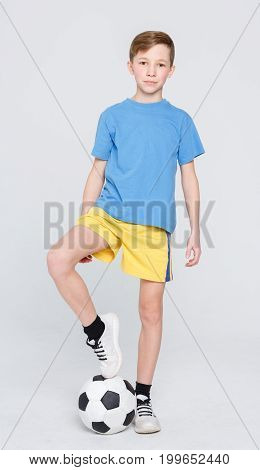 Young football player posing on camera. Handsome boy in sportswear with soccer ball over white studio background. Active and sporty lifestyle concept. Vertical, copy space