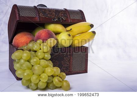 Wooden chest full of fruit like grapes pears peaches and bananas