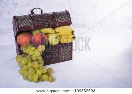 Chest full of fruit like grapes pears peaches and bananas on grungy background