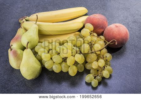 Fruit on top of the kitchen table grapes peaches bananas and pears