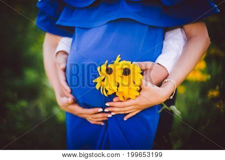 Father And Pregnant Mother Holding Hands Together With Yellow Flowers On A Green Meadow.