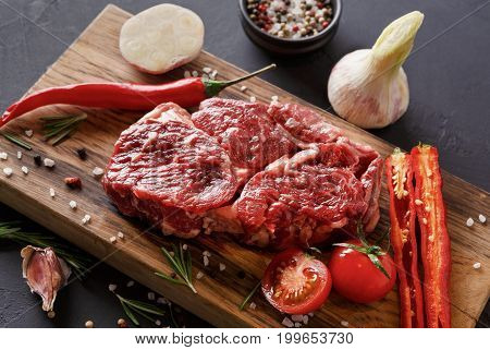 Raw rib eye steak with herbs and spices closeup. Cooking ingredients for restaurant dish. Fresh meat, salt, rosemary, chilli, cherry tomato and garlic on wooden board at black. Stylish food background