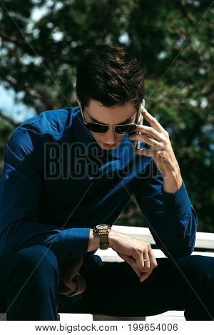 Handsome young man sits on a bench in a summer park talking on his smartphone and looking at his wristwatch. Fashion shot. Business style.
