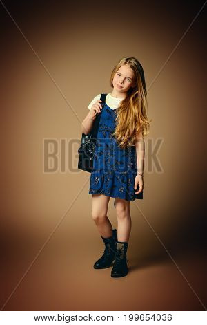 Children's fashion. Cute eight year old girl with long blonde hair posing in summer dress and a bag. Studio shot. Full length portrait.