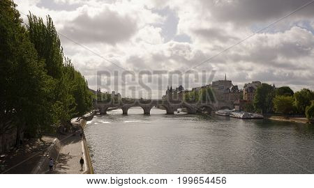 ParisFrance- April 30 2017: View of the island of Site. Pedestrians on the embankments ships sail on the Seine
