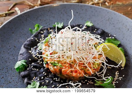 Exclusive restaurant food. Traditional hawaiian appetizer - poke with fresh salmon on black sesame flat cake on gray plate. Organic healthy meals in modern serving on wooden table background, closeup