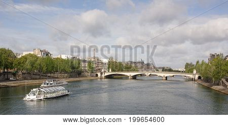 ParisFrance- April 30 2017: View of the bridge Carrousel. People walk along the embankment of the Tuileries. On the Seine ships sail