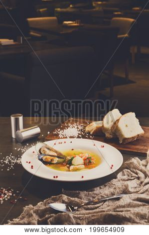 French cuisine restaurant. Seafood soup with white fish, shrimps and mussels in plate sprinkled with spices with hot bread. Freshly cooked exclusive meals on wooden table with linen cloth and spoon