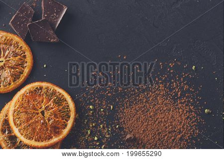 Sweet background. Cocoa powder sprinkled on surface, orange citrons and pieces of dark chocolate on black slate. Top view, copy space
