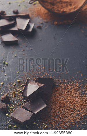 Sweet background. Baking ingredients. Cocoa powder in a sieve and sprinkled on surface, chocolate pieces on black slate, copy space