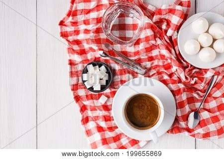 Morning coffee at restaurant. White porcelain cup of black bitter coffee with treats on stylish checkered tablecloth on wooden background, top view, copy space