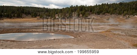 Firehole Lake and clouds reflecting in hot spring pool in the Lower Geyser Basin in Yellowstone National Park in Wyoming United States