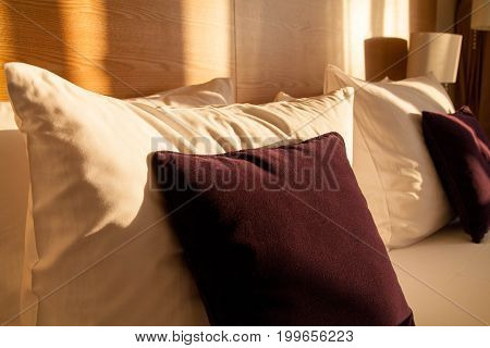 White and bordo pillows at modern bed in room