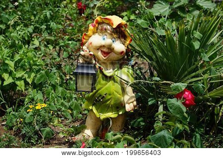 A fun decoration for garden in the form of a dwarf girl with a flashlight
