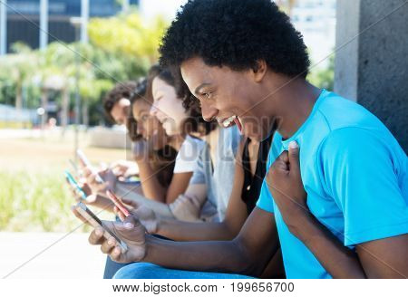 Cheering african american man with cellphone and friends outdoor in the summer