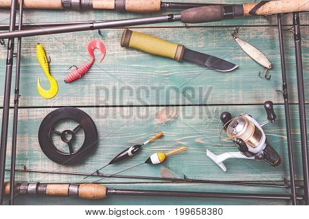 Fishing theme. Frame from fishing rods with fishing tackles, line, knife, reel and fishing buoy on green wooden background