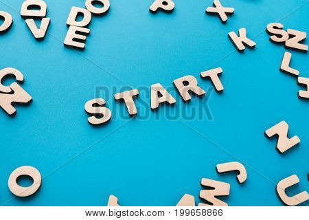 Word Start on blue background, in wooden letters frame. New beginning, startup, challenge concept