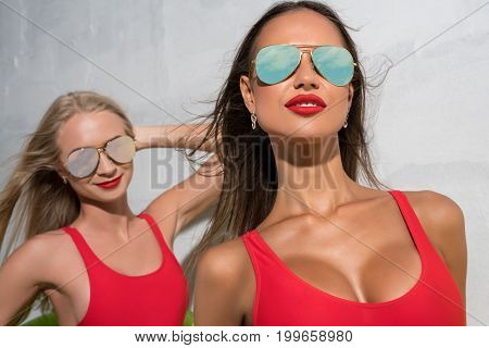 Sexy girls wearing bright swimsuits and glasses sunny photo