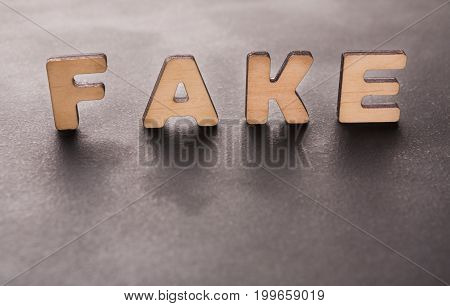 Word Fake standing on table background. Lie, not originality, imitation concept