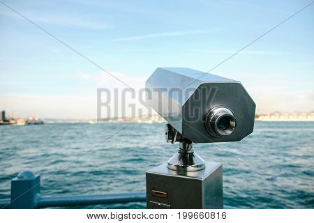 Tourist telescope with scenic view of the sea and blue skies, daytime setting.