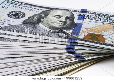 Stack of one hundred dollar bills. Stack of cash money in hundred dollar banknotes. Heap of hundred dollar bills on white background