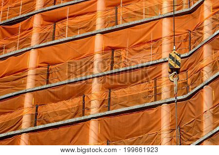 Crane cables and hook against orange mesh of a building under construction background.