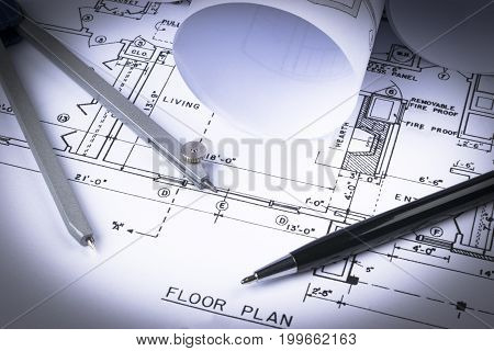 Architectural blueprints and blueprint rolls and a drawing instruments on the worktable. Drawing compass plans. Civil Engineering Construction background.
