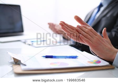Business people clapping, sitting on the desk . Business people.
