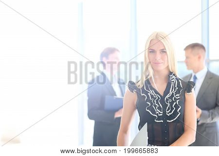 Business woman standing in foreground with a tablet in her hands.