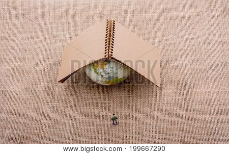 Figurine And Globe With A Notebook