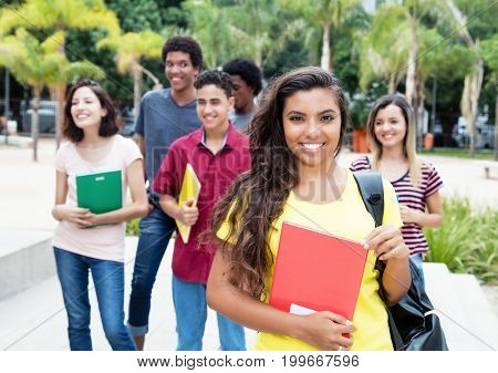 Latin american female student with group of international students outdoor in the summer in the city