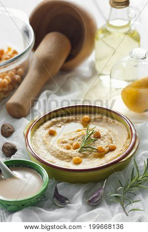 Homemade humus in ceramic bowl with tahina, spices, olive oil, lemon and сhickpea. Selective focus.