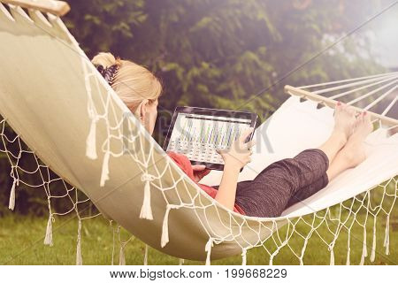 Businesswoman working on a tablet and relaxing in her garden on a hammock (vintage effect)