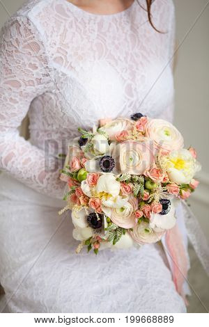 beautiful decorate wedding bouqet in bride hands in white dress