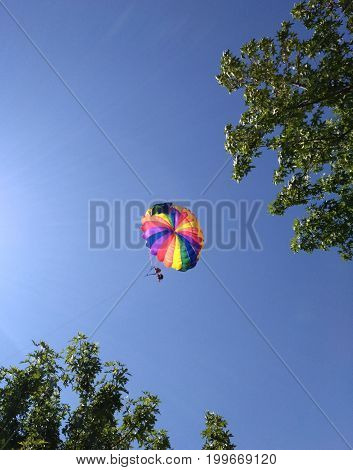 Rest in the sky, two people, a pilot and a passenger flying in the sky under a multi-colored dome of a parachute - a paraglider