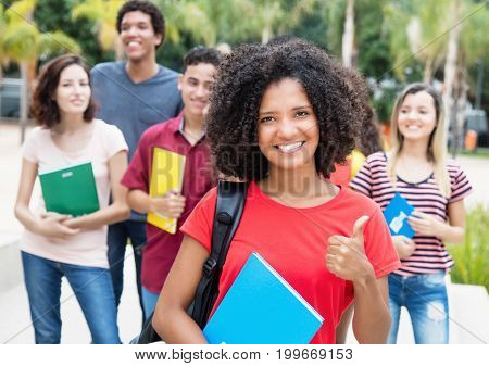 African american female student showing thumb with group of international students outdoor in the summer in the city outdoor in the summer in the city