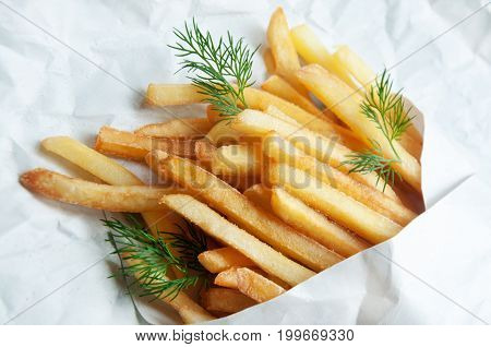Potatoes French Fries Potatoes In A White Paper Bag On A Sheet Of Light Paper.