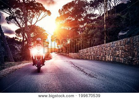 Motorcyclist riding on sunset, enjoying freedom and extreme sport, motorbikers touring, active lifestyle, amazing summer adventure